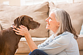 Caucasian woman hugging dog in living room