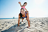 Mother doing push-ups with daughter at beach