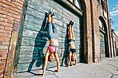 Athletes doing handstand on sidewalk