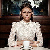Caucasian teenage girl drinking coffee in restaurant