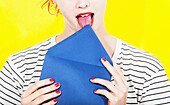 Midsection of woman licking blue envelope against yellow background