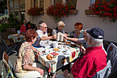 People sit at outdoor table at Cafe Zum Elisaeum at Kloster Kreuzberg abbey