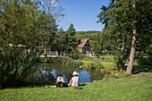People relax along lake at Fränkisches Freiluftmuseum Fladungen open air museum