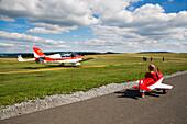 Young boy in toy airplane at Kinderflugplatz adjacent to Flugplatz Wasserkuppe air field