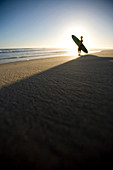 Adam Welch prepares to go for a surf at sunset in Baja California, Mexico.