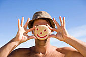 A man holds a smiley face cookie up in front of his face while on a beach in Baja California del Sur.