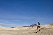 An adult woman running along the moon-like desert floor at Death Valley National Park, California.