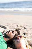 Preston Davis and Landon Astor relax at the beach in Santa Monica , California. The couple is lying with their heads near the shore listening to the waves.