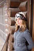 Beautiful Andrejka stands in the doorway of her log house.  With her goggles on she's ready to go snowboarding.