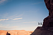Two people jump for joy while hiking in the desert.
