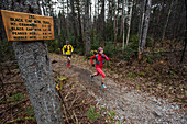 Kristina Folcik and Adam Wilcox running out of the woods on Black Cap Mt. trail.