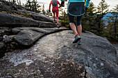 Two women runners on the granite slabs near teh summit of Black Cap Mt. in NH.