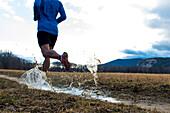 Trail runner splashing through a puddle.
