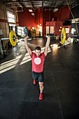 A man weight lifts at a crossfit gym.