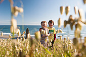 Children standing in wildlowers growing near beach