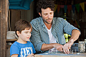 Father watching as young son creates art project with nails and string