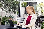 Woman using laptop in hotel courtyard