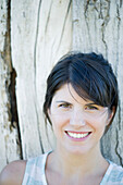 Woman leaning against tree trunk, smiling cheerfully, portrait