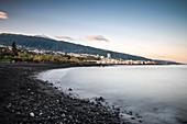 Blick zum Vulkan Teide über Lava Gestein Strand an Atlantik Küste bei Puerto de la Cruz, Teneriffa, Kanarische Inseln, Kanaren, Spanien, Langzeitbelichtung