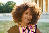 Portrait einer jungen afroamerikanischen Frau im Gegenlicht vor Sehenswürdigkeit, Königsplatz, München, Bayern, Deutschland