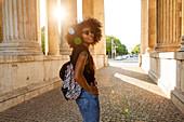 Junge afroamerikanische Frau mit Rucksack im Gegenlicht in der Stadt, Königsplatz, München, Bayern, Deutschland