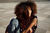Sportliche junge afroamerikanische Frau sitzt cool auf grafischem Boden, Lenbachplatz, München, Bayern, Deutschland