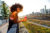Junge afroamerikanische Frau im Gegenlicht lehnt entspannt an Geländer in urbaner Szenerie, Hackerbrücke, München, Bayern, Deutschland