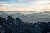 Morning dawn ascending the Barre des Ecrins with views of the Western Alps as far as the Matterhorn, Ecrins National Park, Dauphiné, France