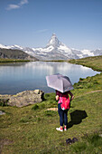 A taiwanese visitor at the Stellisee near Zermatt with views of the Matterhorn, Pennine Alps, canton of Valais, Switzerland