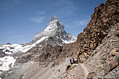 Two hikers on their way to the Hörnli Hut, in the background the Matterhorn, Pennine Alps, canton of Valais, Switzerland