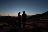 A couple in front of the Borgna Hut at sunset, Val Verzasca, Lepontine Alps, canton of Ticino, Switzerland