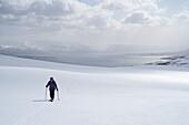 A female skitourer in the valley named Karlsdalur near Dalvík, Tröllaskagi or in English Troll Peninsula, Iceland