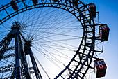 The Ferris wheel, big wheel in the Vienna Prater, Wiener Prater, Amusement Park, against sunlight and clear blue sky, Vienna, Austria