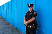 New York policeman with full equipment and blue sunglasses in front of a blue fence looks seriously in the camera, New York City, New York, USA