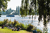 A historical excursion steamer on the inner-city lake Außenalster passes people on the shore enjoy their leisure time, Hamburg, Germany