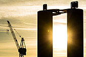 Silhouette, a crane of the shipyard Blohm and Voss with a pile in the foreground during sunrise, Altona, Hamburg, Germany