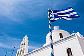 Bell tower and dome built in the traditional blue white style Panagia Platsani church on the Caldera place, with the national flag, Oia, Cyclades, Santorini Greece