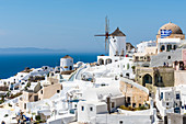 View at in the steep slope situated traditionally built white houses and the windmill, in the background the Mediterranean Sea with the neighbouring island, Oia, Cyclades, Santorini, Greece