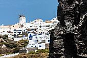 View at the steep coast and the village with the windmill and the traditionally built houses, Oia, Cyclades, Santorini, Greece