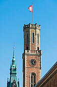 Tower of the Alte Post (former post office) with Hamburg flag and in the background the tower (112-m-high) in the historical style of the neorenaissance built city hall, Hamburg, Germany