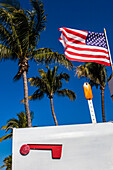 Typical American mailbox with national flag and palms in the background, Naples, Florida, USA