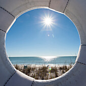 View through a lifebelt at a lonesome beach during sunshine at the golf of Mexico, Naples, Florida, USA