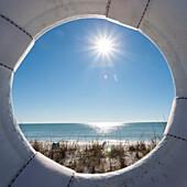 Blick durch einen Rettungsring an einem einsamen Strand im Sonnenschein mit Blick auf den Golf von Mexiko, Naples, Florida, USA