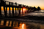 Pier of wood on stilts in the golf of Mexico with many visitors at sunset, Naples, Florida, USA
