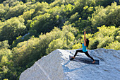 A women performs yoga on a rock outcrop in Little Cottonwood Canyon, Utah.
