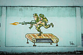 'A hand-painted Cuban wall mural depicts a US soldier shooting an automatic weapon while running on a treadmill marked Vietnam - Yugoslavia - Afganistan - Iraq - Libia''. An Anti-war and anti-US cartoon painted on the wall of a shop in Santa Clara, Villa