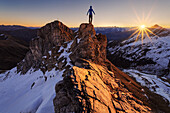 Hiker on a ridge watching the sunset, Tyrolean Alps, Wildlahnertal, Austria