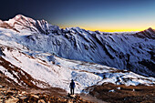 Hiker enjoying the panoramic view at sunset, near Schoeberspitzen in the direction to Steinernes Lamm, over the Tyrolean mountains, Austria