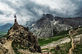 Hiker enjoying venturous view in towards the Rosengarten Group, Dolomites, Unesco world heritage, Italy