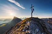 Hiker climbing onto the summit cross at Tulln mountain, watching the sunrise, On the left in the background the Peitler Kofel mountain, Dolomites, Unesco world heritage, Italy